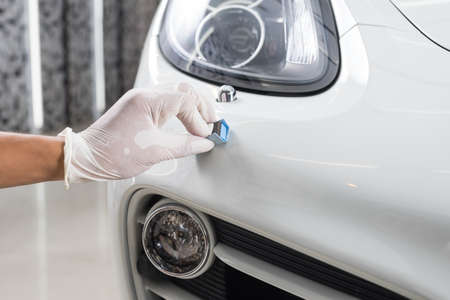 detailing: Car detailing series : Closeup of hand  coating white car bumper Stock Photo