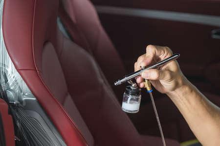 garage automobile: Car série détaillant: Gros plan des sièges d'auto de revêtement de la main Banque d'images