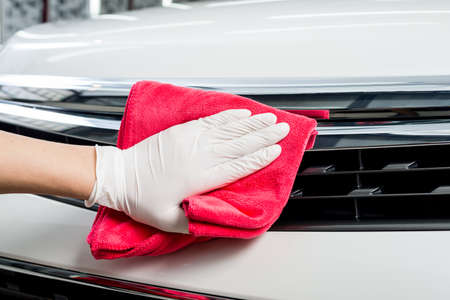 car grill: Car detailing series : Closeup of hand cleaning white car front grill Stock Photo