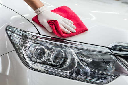 Car detailing series : Worker cleaning white car Archivio Fotografico