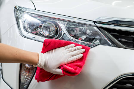 Car detailing series : Closeup of hand cleaning white car bumper Stock Photo