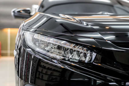 Car detailing series : Closeup of clean headlights of black car