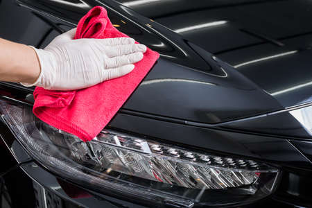 Car detailing series : Closeup of hand cleaning black car paint Stock Photo