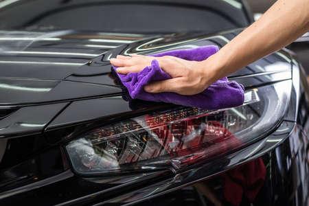 detallando serie de coches: Primer de la mano de limpiar la pintura del coche negro Foto de archivo