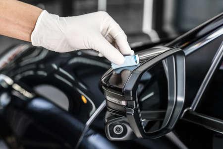 detailing: Car detailing series : Closeup of hand coating black car side mirror