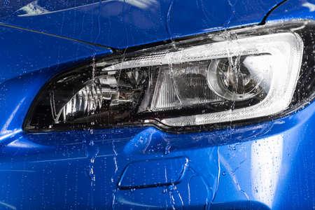 Car detailing series : Water dripping down blue car headlights