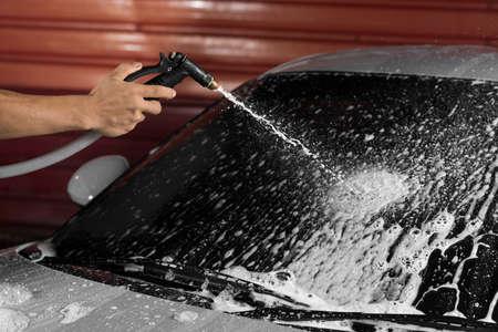 detailing: Car detailing series : Spraying foam on grey car windshield Stock Photo