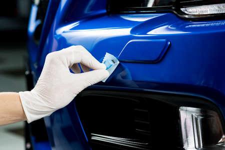Car detailing series : Closeup of hand coating blue car bumper