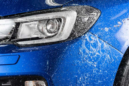 Car detailing series : Water splashing on blue car bumper
