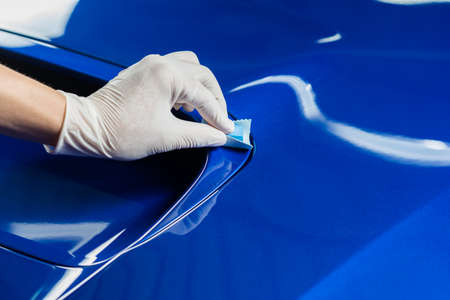 coating: Car detailing series : Closeup of hand coating blue car bonnet
