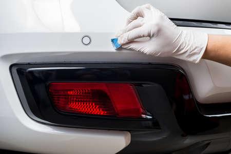 detailing: Car detailing series : Closeup of hand coating white car rear bumper Stock Photo
