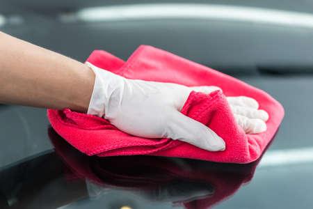 Car série détaillant: Gros plan de la main pare-brise essuyant avec un chiffon en microfibre rouge