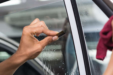 tinting: Car window tinting series : Scraping window surface Stock Photo