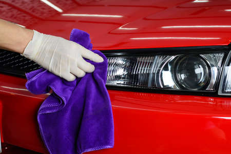 Car detailing series : Closeup of hand cleaning red car paint