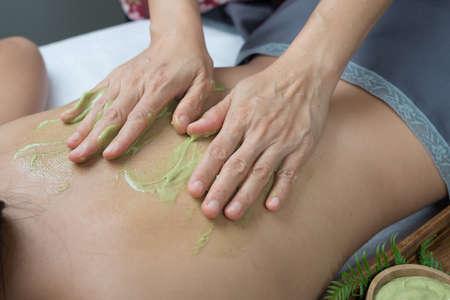 Massage series : Therapist massaging Asian womans back with green tea scrub