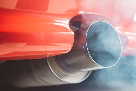 Smoke coming out of red car exhaust pipe