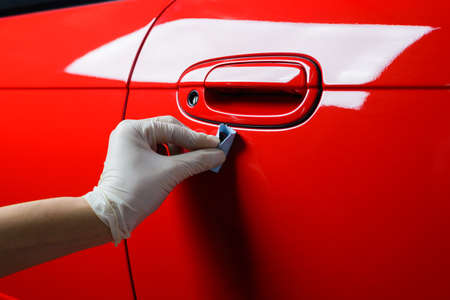 Car detailing series : Closeup of hand coating red car paint Фото со стока