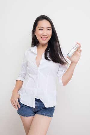 healer: Beauty series: Asian woman holding bottle of moisturizer against white background