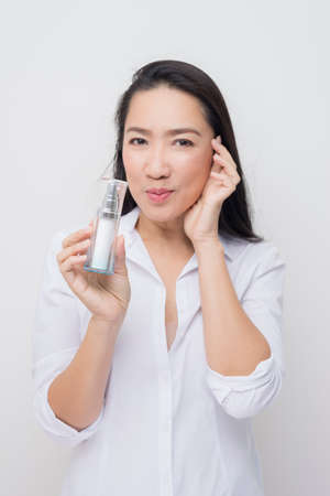 sooth: Beauty series: Asian woman holding bottle of moisturizer against white background