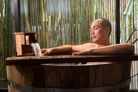 Onsen series: Asian man taking a bath in wooden bathtub Stock Photo