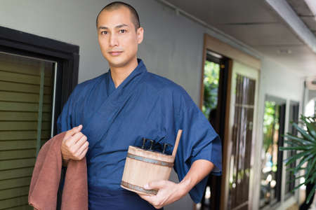 Onsen series: Asian man holding wooden bucket in ryokan Standard-Bild