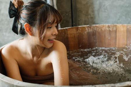 Onsen series: Asian woman relaxing in wooden bathtub