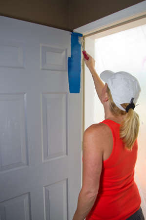 Blond Woman painting the outside of a door blue photo