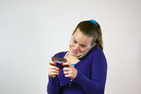 Teen girl with two phones texting and talking photo