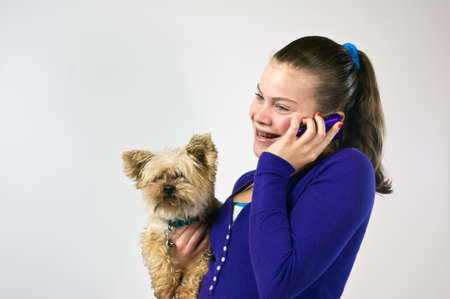 Teen girl talking on the telephone and holding a small dog photo
