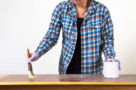 Woman sanding and varnishing a table photo