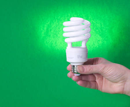 Closeup of a compact fluorescent bulb against a green background photo