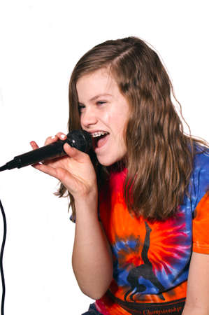 Teen Girl singing in a microphone with tie dye shirt isolated against white background photo