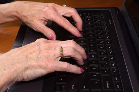 Close up of Senior citizen hands on laptop keyboard photo