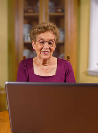 Senior citizen using laptop in dinning room photo