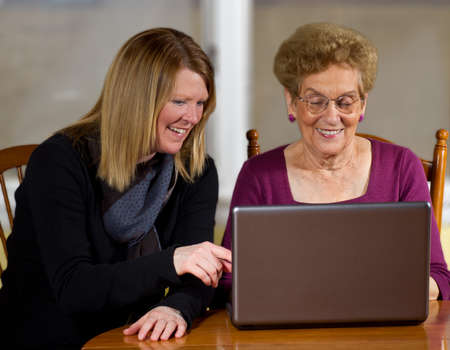 Daughter teaching elderly mother to use laptop