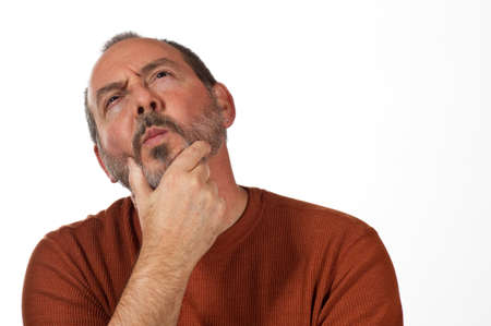 perplexed: middle aged man with hand on beard looking up thinking Stock Photo