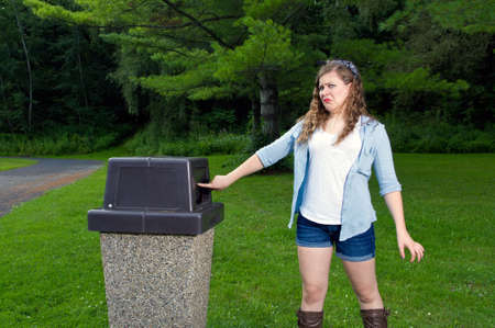 Teen Girl  in a park looking in a trash can with a disgusting look on her face Stock Photo