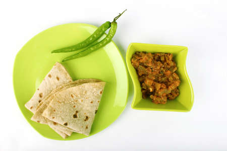 atta: Indian roti and green fried vegetable on white background