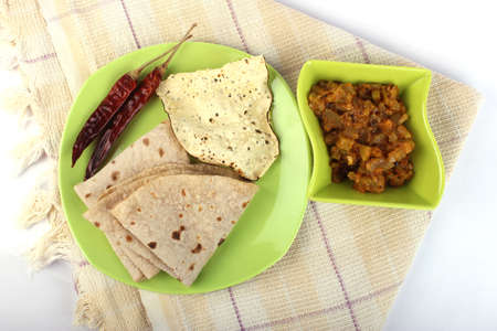 Indian roti and green fried vegetable on white background