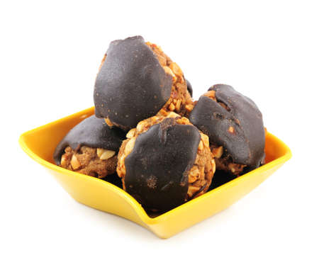 chocolate cookies with peanuts in yellow bowl isolated on white