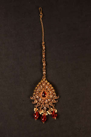 Authentic Traditional Indian Jewellery Tika On Dark Background. Wear in Head in Wedding, Festivals And Other Occasion. Very Useful Image For Website, Printing & Mobile Application.
