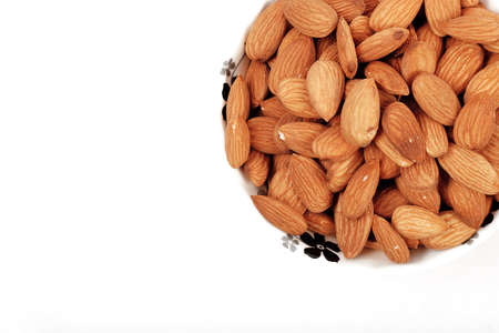 Group of almonds inside and outside bowl isolated on white. Stock fotó