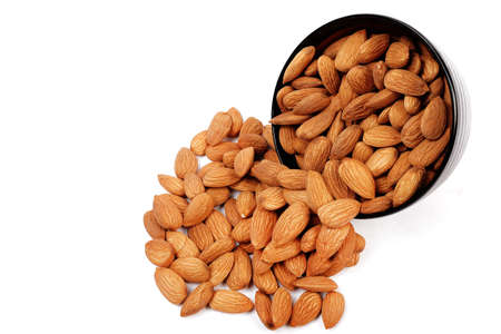 Group of almonds inside and outside bowl isolated on white.