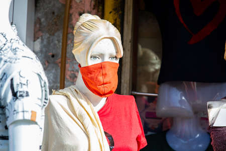 Female Mannequin with mask on face. Shops are reopening after lock down restrictions due to the covid-19 pandemic, back to normal life with few safety measure. Stockfoto
