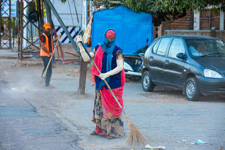 Jodhpur, Rajashtbn, India. 30 March 2020: A woman sweeping the city road in the morning manually with a traditional broom.Coronavirus, covid-19 situation. Editorial