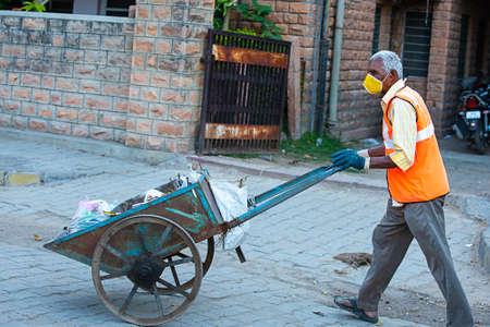 Jodhpur, Rajashtbn, India. 30 March 2020: Indian man wearing mask pulling hand cart full of garbage cleaning city roads, Coronavirus, Covid-19 outbreak, Swachh Bharat Mission. Editorial