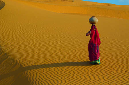 Indian woman carrying heavy jug of water on her head and walking on a yellow sand dune in the hot summer desert against blue sky.water crises, rajasthan, india