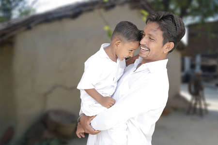 Happy rural indian young father and little son looking at each other and laughing, hugging, both wearing white traditional cloths with village background, copy space to write text.