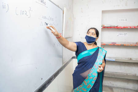 Female Teacher Wearing Mask and teach pointing on whiteboard in classroom, Indian school education class during covid19 pandemic, new normal, copy space.