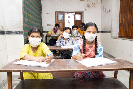 Indian Students Studying In Classroom Wearing Mask And Social Distancing, school reopen during covid19 pandemic Editorial